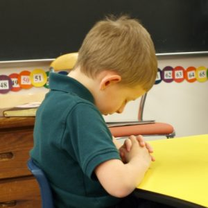 Boy praying at desk