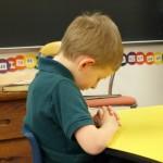 Boy praying at desk